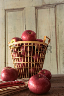 Red apples in metal basket on kitchen table
