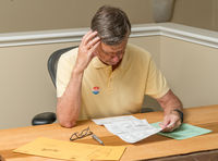 Senior caucasian man sitting at his desk and completing absentee voting ballot