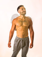 Male muscular angel with white wings in studio shot
