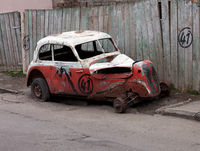 Broken vintage car on dirty roadside