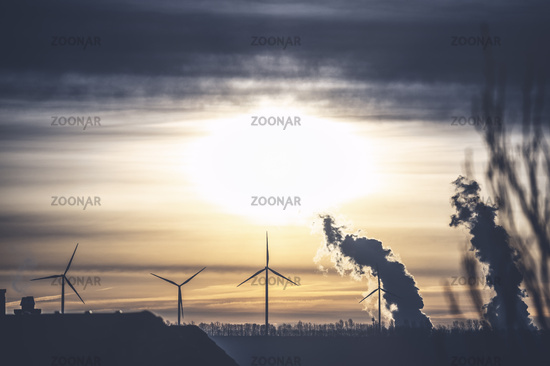 Wind turbines and steam flags of a power plant against the light