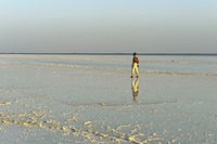 Tourist walkign across the salt crust on Lake Assale,Danakil depression, Afar Triangle, Ethiopia