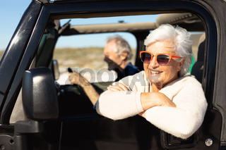 Old couple with a car at the beach