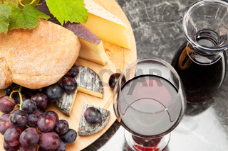 Red wine with wine grapes cheese plate and bread