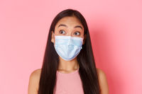 Covid-19 pandemic, coronavirus and social distancing concept. Close-up of curious and surprised attractive asian girl in medical mask, looking upper left corner intrigued, pink background
