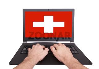 Hands working on laptop, Switzerland