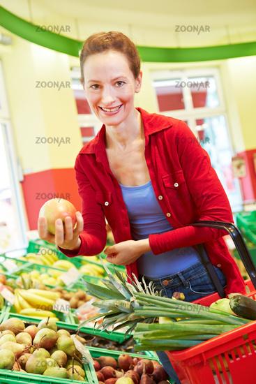 Ältere Frau hält Apfel im Supermarkt
