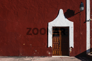 Red Colonial building with wooden door, Valladolid, Yucatan, Mexico