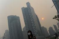 Singapur, Republik Singapur, Frau mit Atemschutzmaske im Smog verschleierten Geschaeftsviertel von Marina Bay