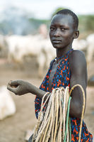 MUNDARI TRIBE, SOUTH SUDAN - MARCH 11, 2020: Teenager in traditional garment carrying ropes and looking at camera while working near cattle on pasture of Mundari Tribe village in South Sudan, Africa