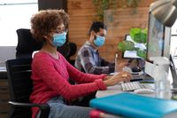 Mixed race woman wearing face mask using computer at desk in office