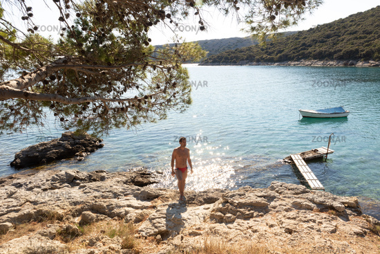 Young sporty man wearing red speedos tanning and realaxing on wild cove of Adriatic sea on a beach in shade of pine tree