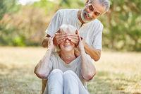 Senior hält Frau die Augen zu