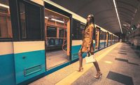 Walking in to an open doors of an empty subway train beautiful young girl with long beautiful legs in a yellow spring coat and a white handbag or purse in hand