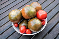tomatoes in a bowl on a wooden table