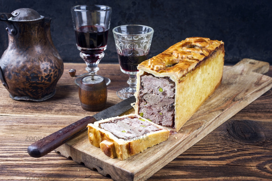 Traditional French Pate en croute with goose meat and liver as closeup with red wine on a wooden board