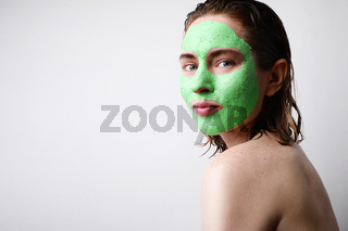 Portrait of happy woman with moisturising avocado green facial mask isolated on pink background. Beauty and skin care.