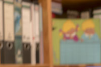 Blurred colorful background of a nursery shelf with folders and timetable