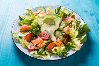 Healthy salad with smoked samlmon and avocado on cyan vackground