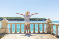 Rear view of happy woman on vacation, wearing straw summer hat ,standing on luxury elegant old stone balcony of coastal villa, relaxing, arms rised to the sun, looking at blue Adriatic sea