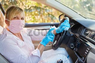 Putzkraft desinfiziert und wischt Lenkrad von Mietwagen wegen Coronavirus