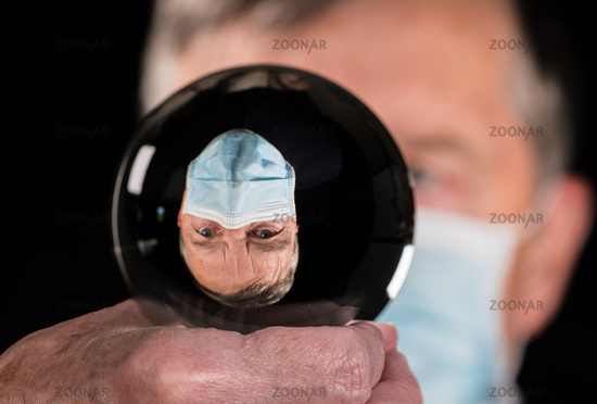 Senior man wearing a medical mask inside a glass crystal ball to show that he chooses to be protected