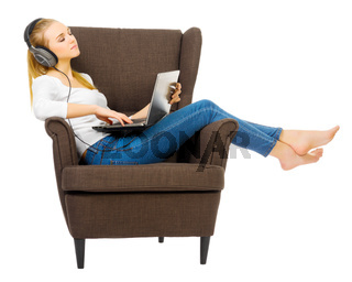 Young girl with headphones listen music on chair isolated