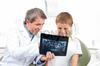 Zahnarzt erklärt Kind Röntgenbild