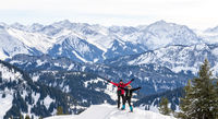 Senior couple is snowshoe hiking in alpine snow winter mountains panorama. Happy successful People with outstrechted arms. Allgau, Bavaria, Germany.