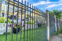 Black metal fence with potted colorful flowers against blurry homes and blue sky