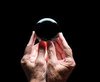 Hands holding a crystal glass forecasting ball with black center to allow easy composites