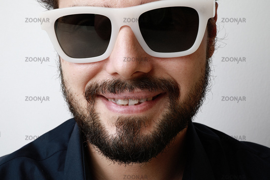 Close-up of handsome young man with beard in blue shirt wearing sunglasses looking with happy expression in camera.