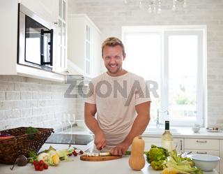 Man cooking at home preparing salad in kitchen