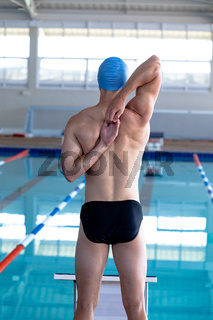Swimmer stretching in front of the pool