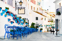 Mijas Pueblo Blanco, charming small village, picturesque empty street in old town with bright blue tables chairs of local cafe, flower pots hanging on white washed houses walls, Costa del Sol, Spain