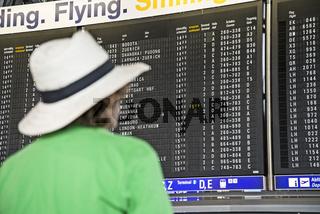 Teenager schaut auf Anzeigentafel im Flughafen