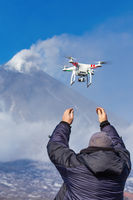 Male launches flying drone quadcopter UAV with digital camera on background of volcano eruption