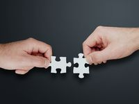 hands of two people putting together two jigsaw puzzle pieces