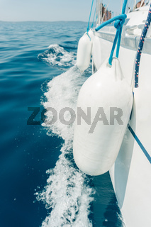 View down the side of a sailboat. Close up to the fenders. Travel and vacation concept.