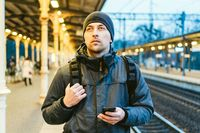 Train Station in Sopot, Poland, Europe. Attractive man waiting at the train station. Thinking about trip, with backpack. Travel photography. tourist with backpack stand on railway station platform