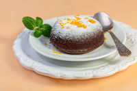Warm chocolate dessert with orange peel and mint.