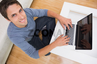 Overhead portrait of a man using laptop in living room