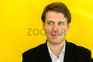 Portrait of young handsome businessman against yellow background