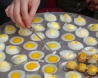 A street vendor cooks poached quail eggs