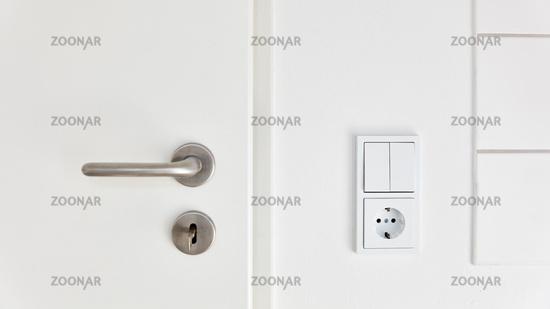 Lichtschalter und Steckdose neben Tür in Küche oder Bad