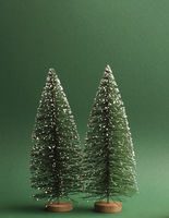 Two fir trees with snow on a green paper background, space for text on top