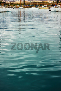 Marina - Water surface with ripple and reflection of yachts