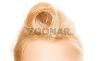 Pin-up hairstyle. Closeup of female blond hair bun