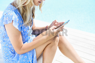 Stylish woman using smartphone in sunny day