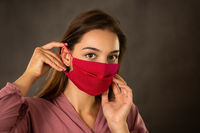 Woman attaching red cloth face mask on ear with fingers with dark background